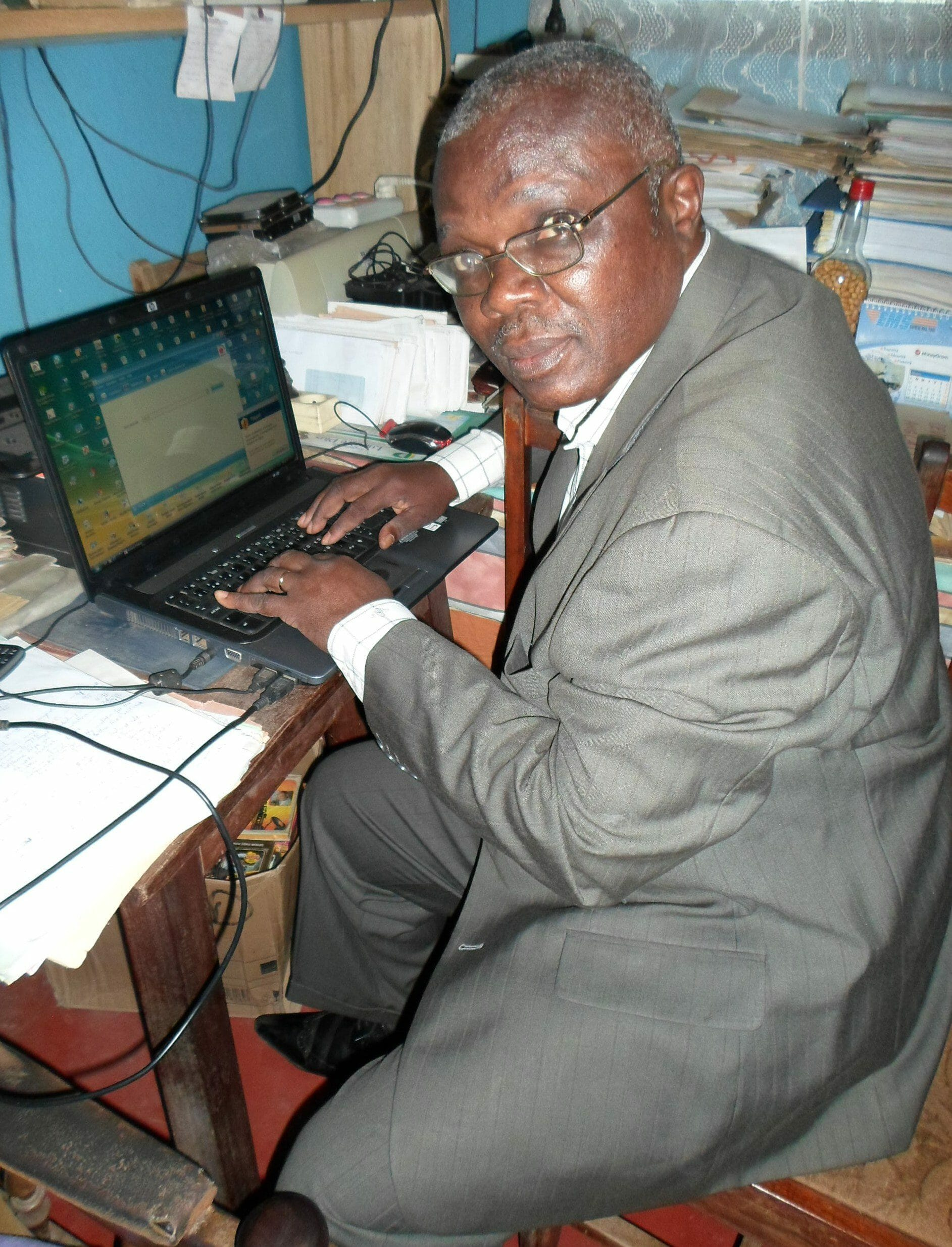 Photo of me Akoli in suit and working on a laptop in my home office to signify about Akoli