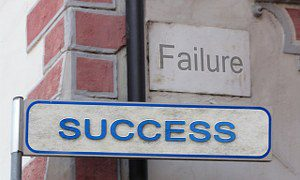 Signs on a wall reading Failure and SUCCESS