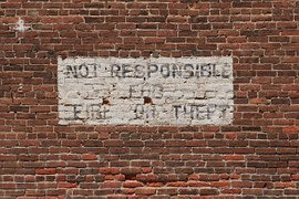 "The words ""Not responsible for fire or theft"" written on a whitewahsed part of a birck wall to signify Disclaimer and Disclosure."