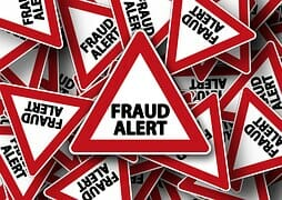 A road sign reading Fraud Alert