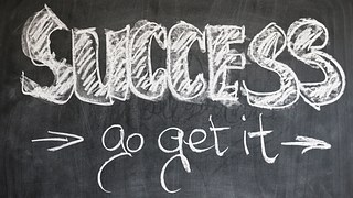 "The words ""SUCCESS > go get it > written in chalk on a black board."