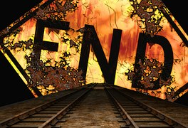 "the word ""End"" written in black against a tropical sunset scene at the end of railroad tracks."