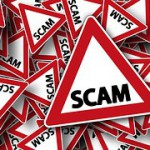 """A road stop sign reading """"Scam"""""""