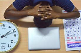 A worker with the head on the laptop on his desk, a calendar to his left and a clock by his right.