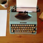 A typewriting machine on a table with a paper inseted into its roller and a sheet and a cup of coffee beside it to signify writing.