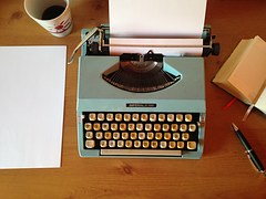 A typewriting machine on a table with a paper inseted into its roller and a sheet and a cup of coffee beside it to signify amplifying writing efficiency