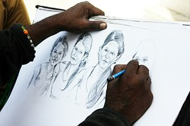 An artist using a pencil to make sketches of women