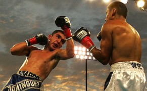 A boxer giving an uppercut but apprently going down to the canvas