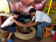 A craftsman teaching a child to make pots, with dried ones behind them