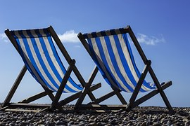 2 vacation chairs with with white and blue striped canvas on a beach to signify comfort zone.