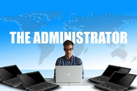 """A person sitting in front of a world map with the words """"The Administrator written on it and in front of a white laptop surrounded by 2 black laptops on the left and right"""