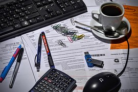 A bookkeeper's desk covered with accounting documents on which are a keyboard, pens, a cup of coffee, a calculator, mouse, and paper clips.