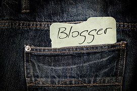 "The word ""blogger"" written on a piece of white paper tucked into the back pockets of a blue jeans pants"