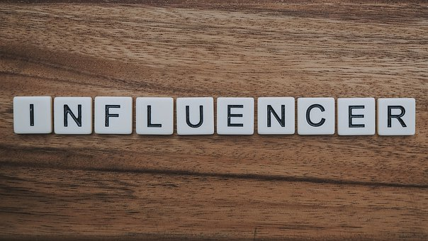 INFLUENCER written on white cubes on a mahogany desk top for 26 major influencers to follow