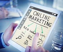 A pair of hands holding a carboard sheet with ONLINE MARKETING written on it and its various ramifications such as SEO, etc.