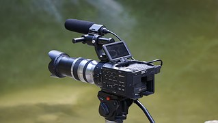 A digital video camera on tripods in action.