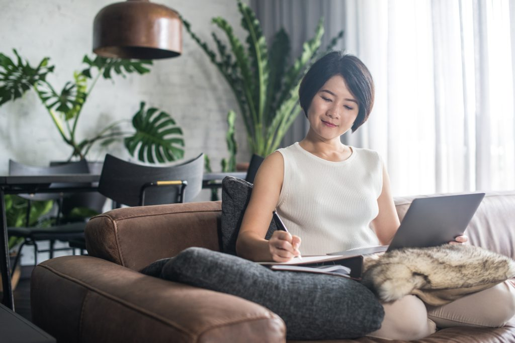 A woman writing in her home from her couch with a laptop opened on her lap signifying How to Make a Living From Home: 6 (Legit) Online Job Ideas