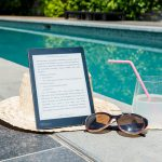 An ebook laid on a beach hat beside sunglasses, a drink with a straw and a swimming pool