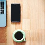 Part of a laptop keyboard at the left, a portable phone and a cup of coffee on a desk to signify work from home