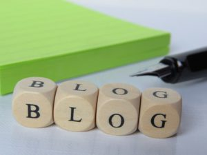 The word BLOG written on 4 dices beside a black pen and a green bag