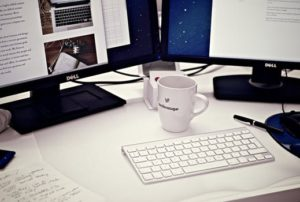 A cup mug behind a wireless keyboard and in front of two computer screens as content matters
