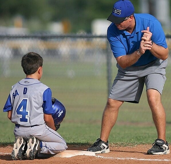 A coach teaching a child how to thrwo the ball signifying the value of coaching to succeed at wealthy affiliate