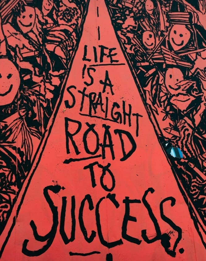 Drawing in red colour of people smiling around a triangle with the words Life is a straight road to success