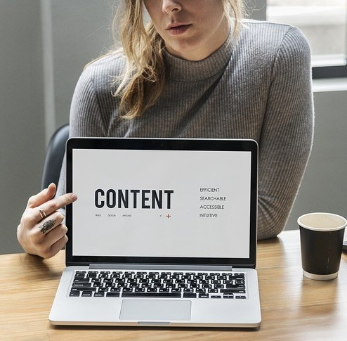 Lady in a browN sweater pointing to the word CONTENT on her laptop screen to signify How Can You Write Content Faster and More Efficiently