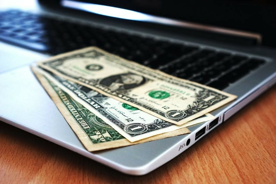 One dollar bills on an opened  laptop