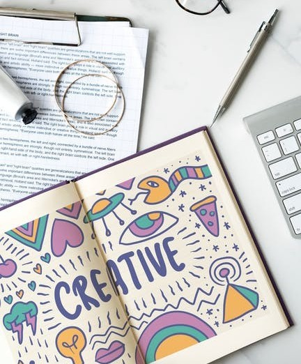 Open book with the word CREATIVE surrounded by simple designs and other objects on a table to signify Maximum Content Creation Efficiency in How Can You Write Content Faster and More Efficiently?