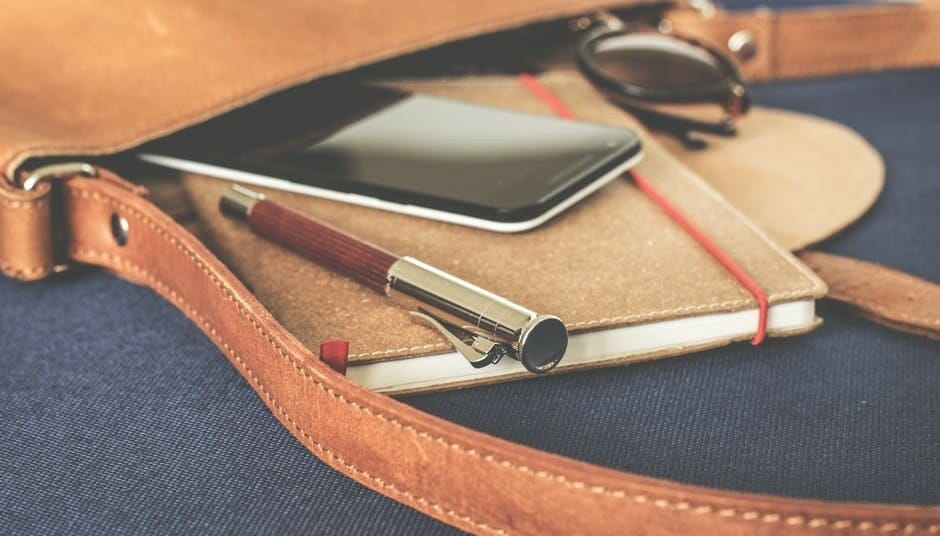 Pen and smartphone lying on a notebook to signify How to Create Content with Intent That Profits You