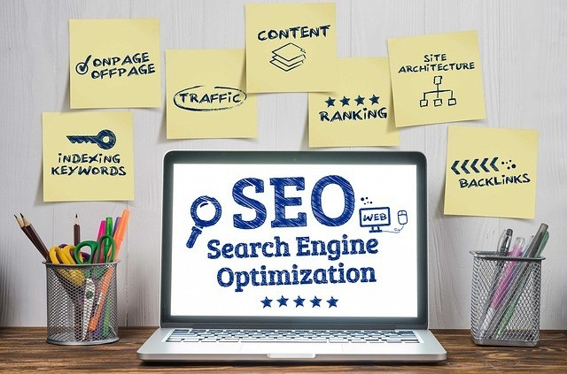 SEO written on a laptop screen surrounded by stickerswith words like On pageseo on them to signify content optimization in How Can You Write Content Faster and More Efficiently