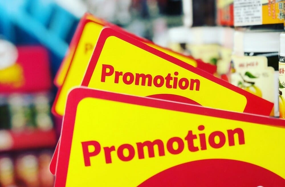 Yellow rectangumar piece of cardboard with the word Promotion written in red over it to signify how to incorporate effective sales promotion