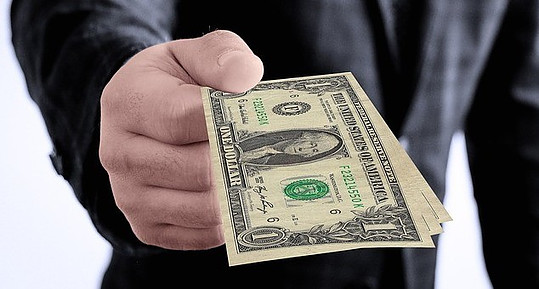 A hand holding out a dollar bill to signify intern,et marketing