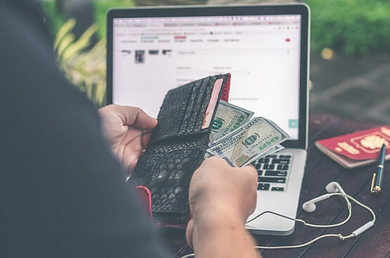 Lit laptop screen witha man sitting before it extracting bills from a wallet to signify Summary List of Affiliate Marketing, Best Way to Make Money Online