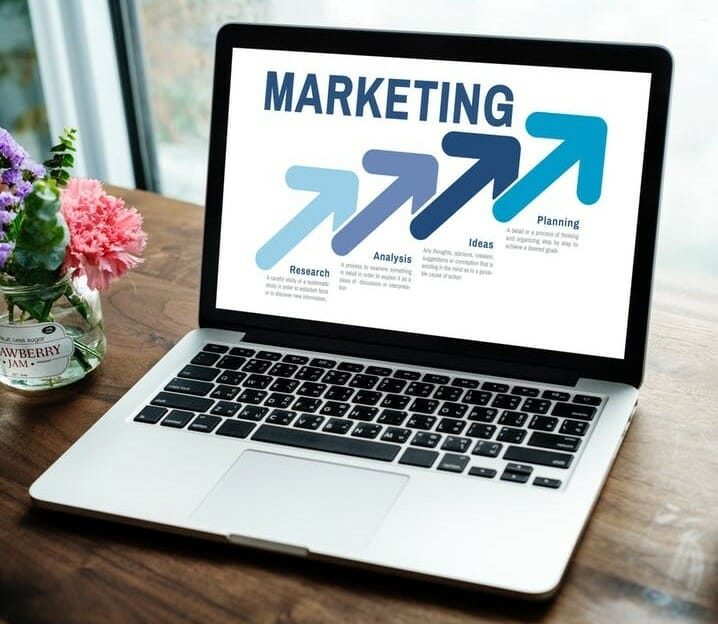 MARKETING written on a laptop screen with three up-pointing arrows to signify  all about internet marketing