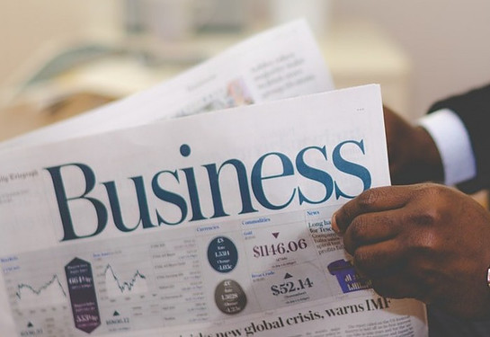 A hand holding a newspaper with the title Business to signify Summary list of 90 Reasons Why 90 Percent of Online Businesses Fail - Part I