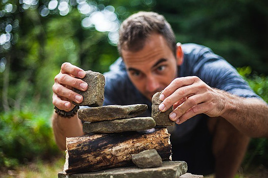 Man carefully laying stones to balance them to signify MLM - Is Network Marketing Easy?