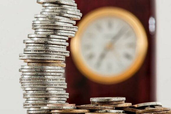 pile-of-coins-before-ablurry-clock-to-signify-7-ways-to-reach-your-mlm-goa