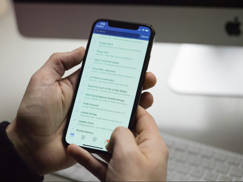Person consulting a list of messages on an iphone to signify Structure opt-in list and affiliate marketing - effective internet marketing plan