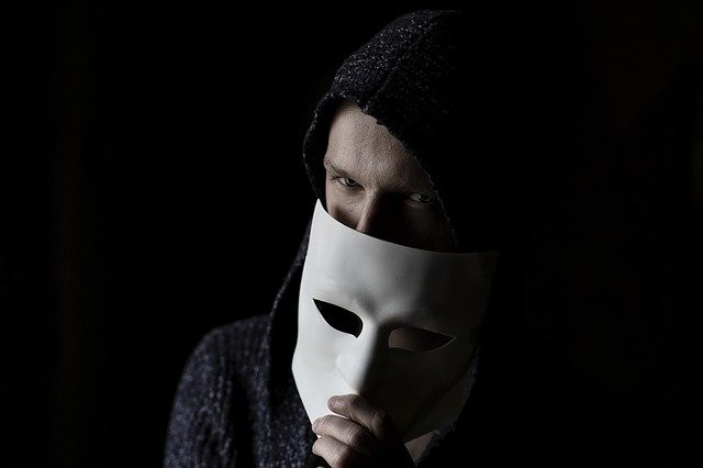 Man before dark background covering face with mask to signify How to keep away from Affiliate Marketing Rip-offs