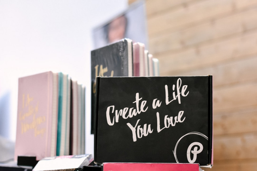 Stack of books with black slate 'Creare a life you love' to signify Being an Affiliate Marketer and the Benefits