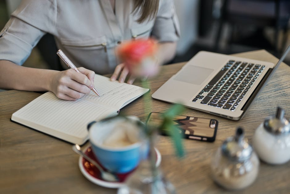Somebody writing at a table to mean How to Create Content that Captivates Readers