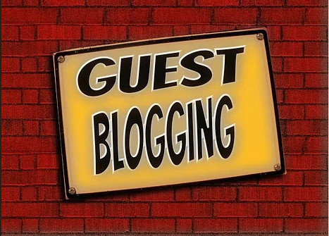 GUEST BLOGGING written on a yellow reclining sign on a brick wallign