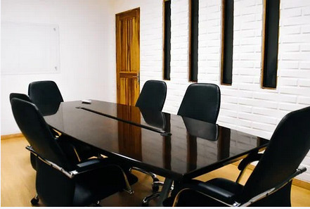 Businessofficewith shinytable surroundedby 5 leather chairs